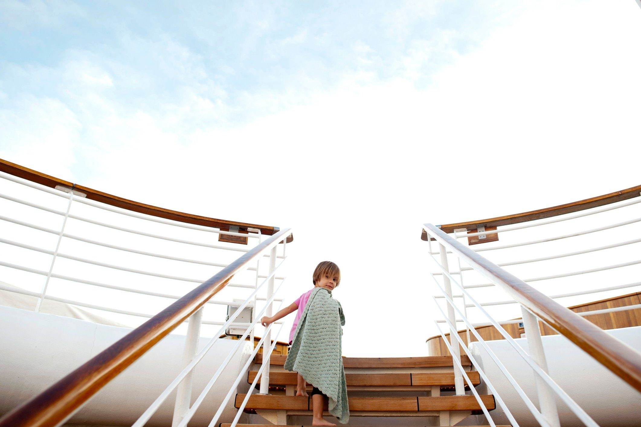 Low angle view of girl climbing steps in cruise ship against sky