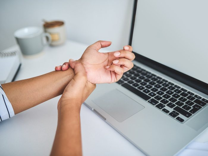Carpal tunnel syndrome symptoms and treatments - close up of woman suffering from carpal tunnel syndrome