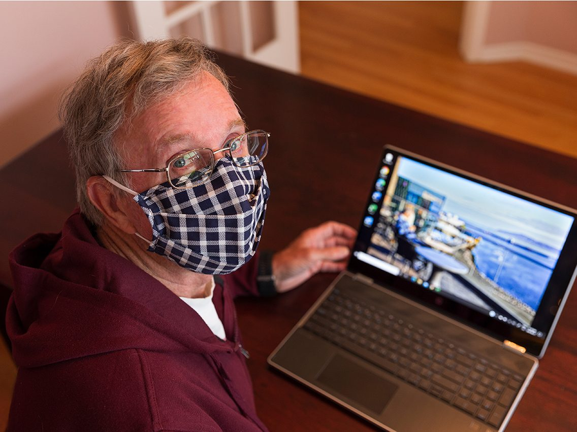 Face mask selfies from across Canada - man in mask with laptop
