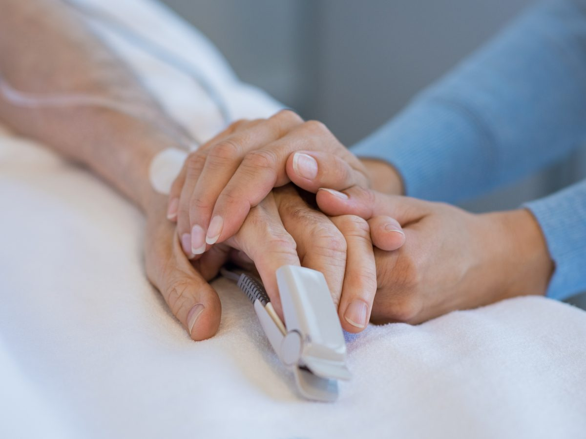 Daughter holding the hand of an elderly father