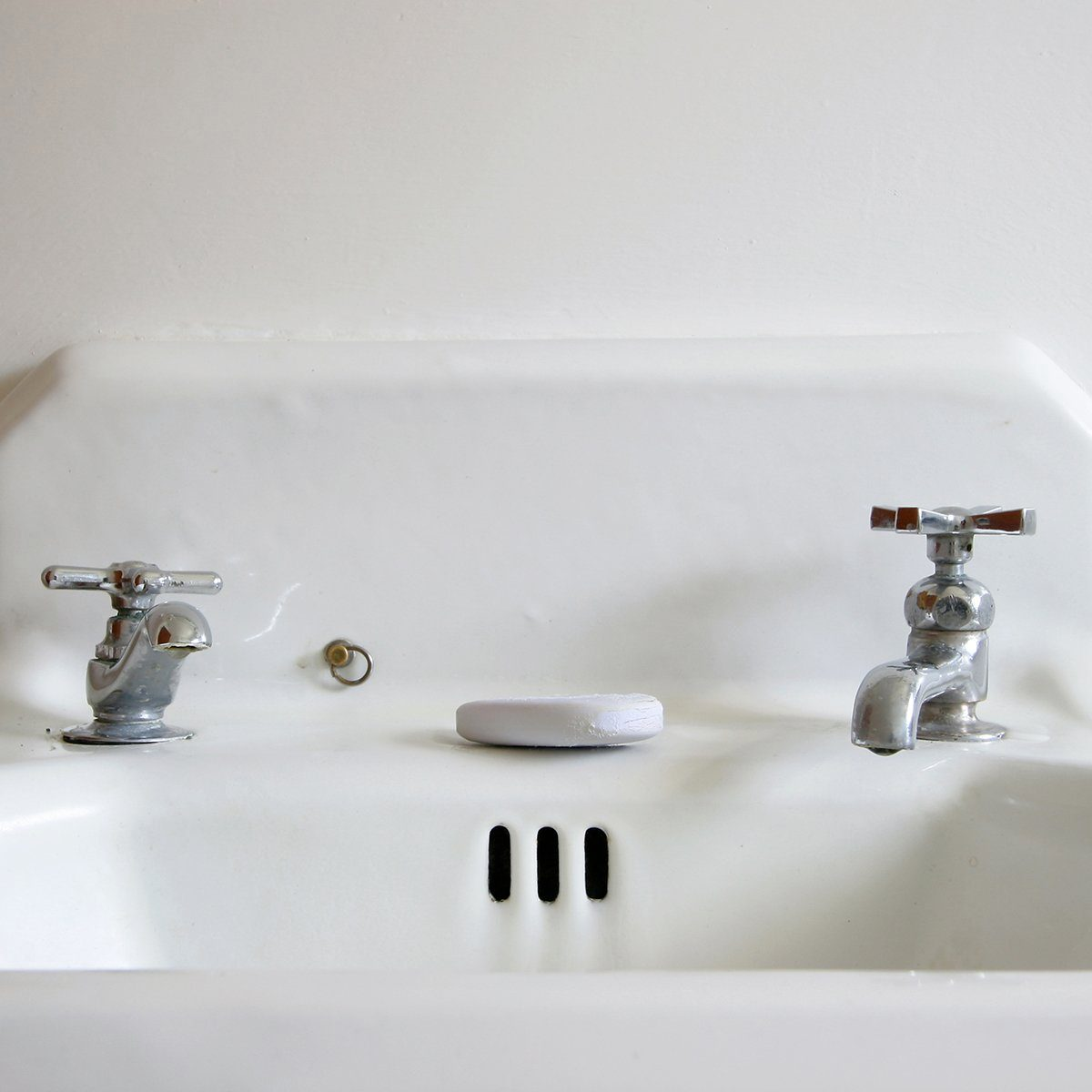 A retro white sink with old fashioned faucets and a bar of soap.