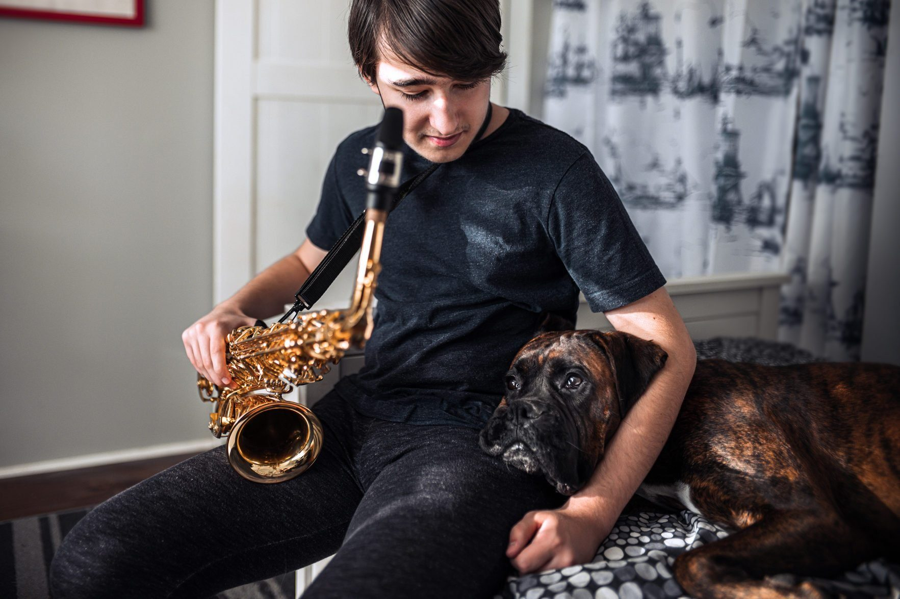 Most affectionate dog breeds - Teenager playing sax in his room