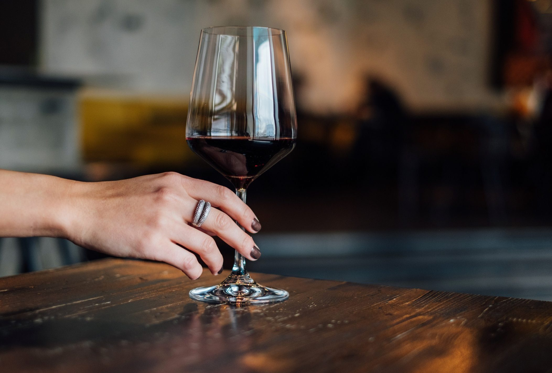Close-Up Of Hand Holding wine glass On Table