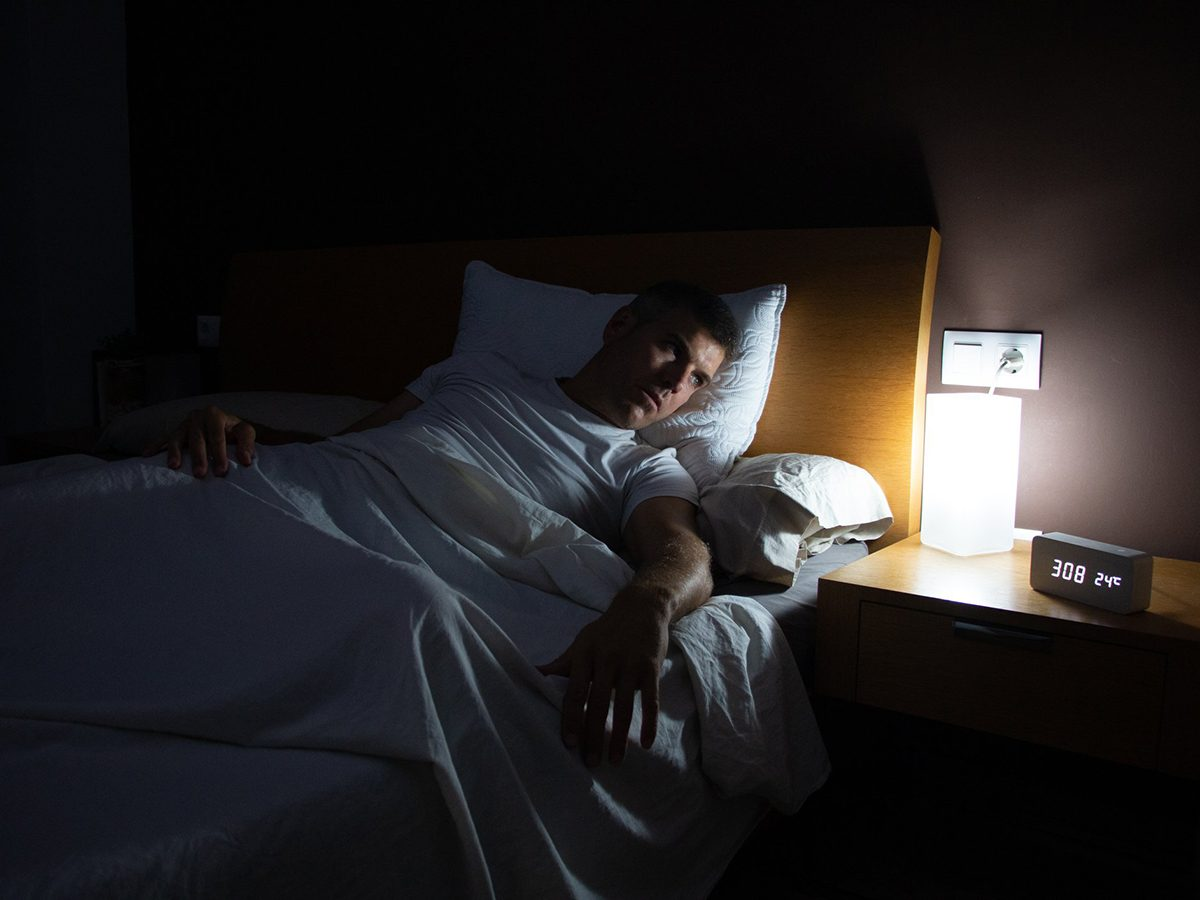 Anxiety at night - A man with insomnia looks at the clock at dawn from the bed with concern