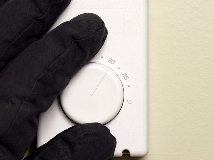 Best temperature for a house in winter - hand with glove changing thermostat