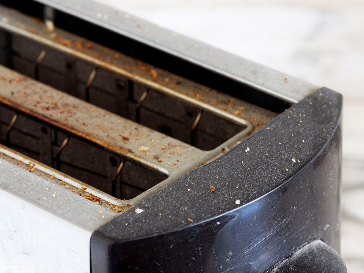 Common toaster mistakes - dirty kitchen toaster covered in dust and bread crumbs