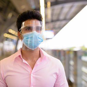Do face shields really stop coronavirus - man wearing mask and face shield at train station