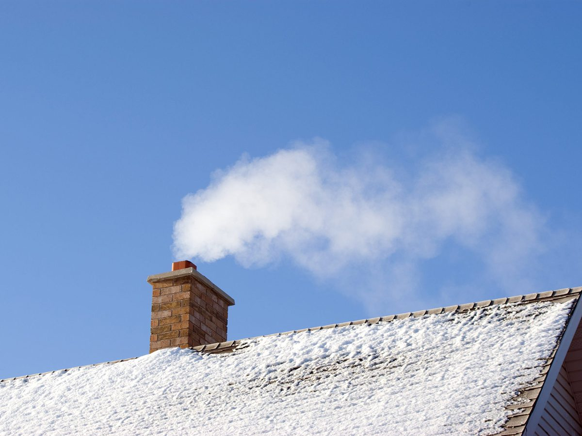 Home fire hazards - White smoke comes out of a house's chimney on a winter day.