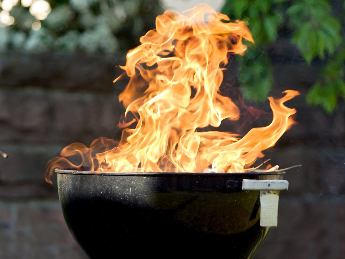 Home fire hazards - Raging flames from charcoal barbecue grill.