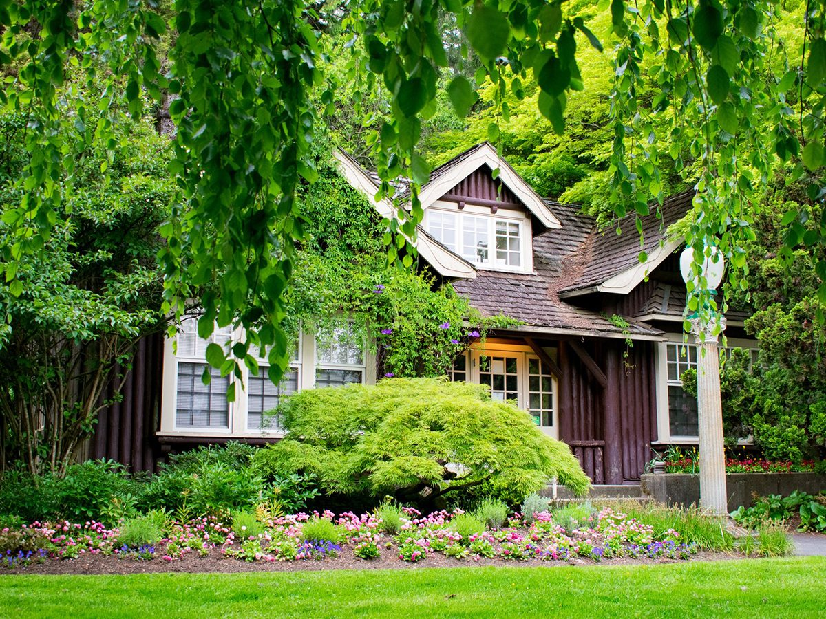 Home fire hazards - A quaint fairytale cottage, covered by lush plant life and flowers, in the Rose Garden at Stanley Park, Vancouver, British Columbia, Canada.