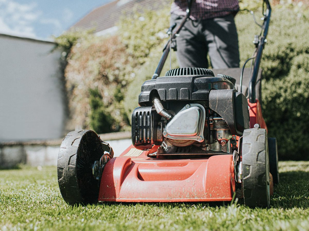 Home fire hazards - Man mowing the grass with a manual petrol lawnmower.