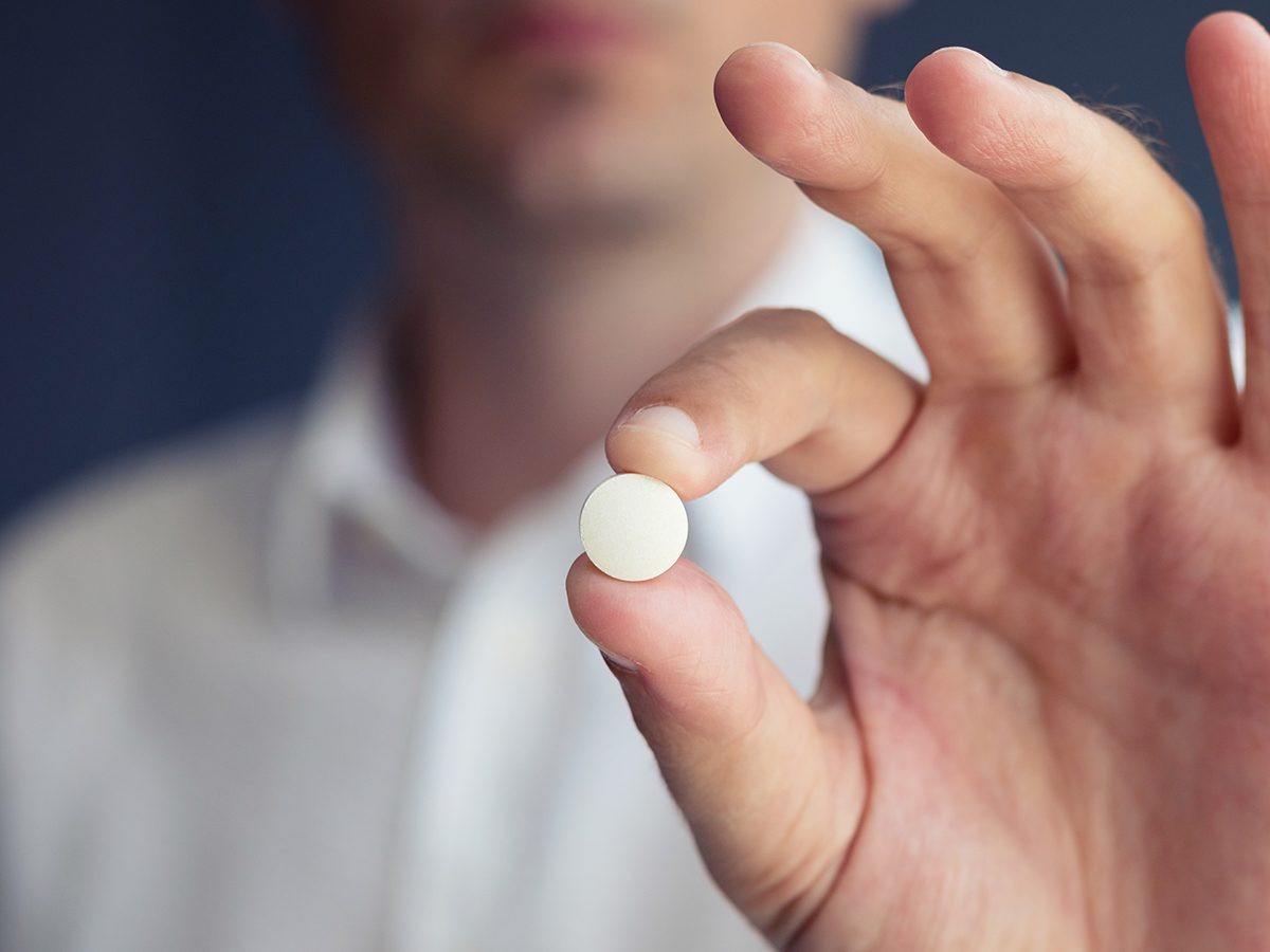 Health news - man holding acetaminophen tablet