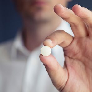 Medical news - man holding acetaminophen tablet