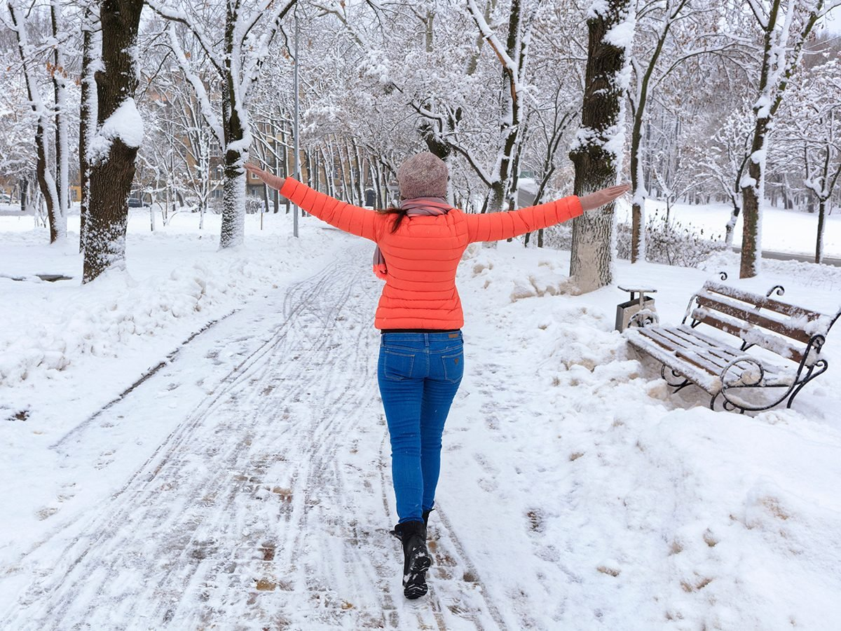 Health news - woman walking through park in winter