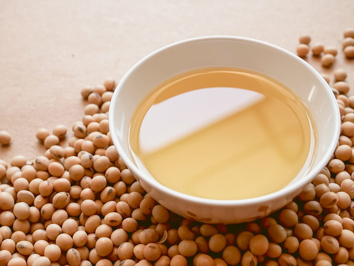 Healthiest cooking oil - oil and soy beans on brown paper