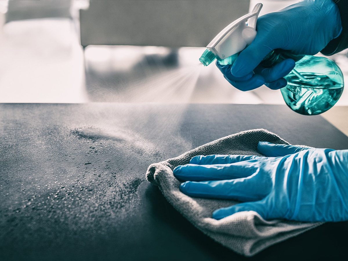 Mistakes you're making with disinfection - Surface sanitizing against COVID-19 outbreak. Home cleaning spraying antibacterial spray bottle disinfecting against coronavirus wearing nitrile gloves. Sanitize hospital surfaces prevention.