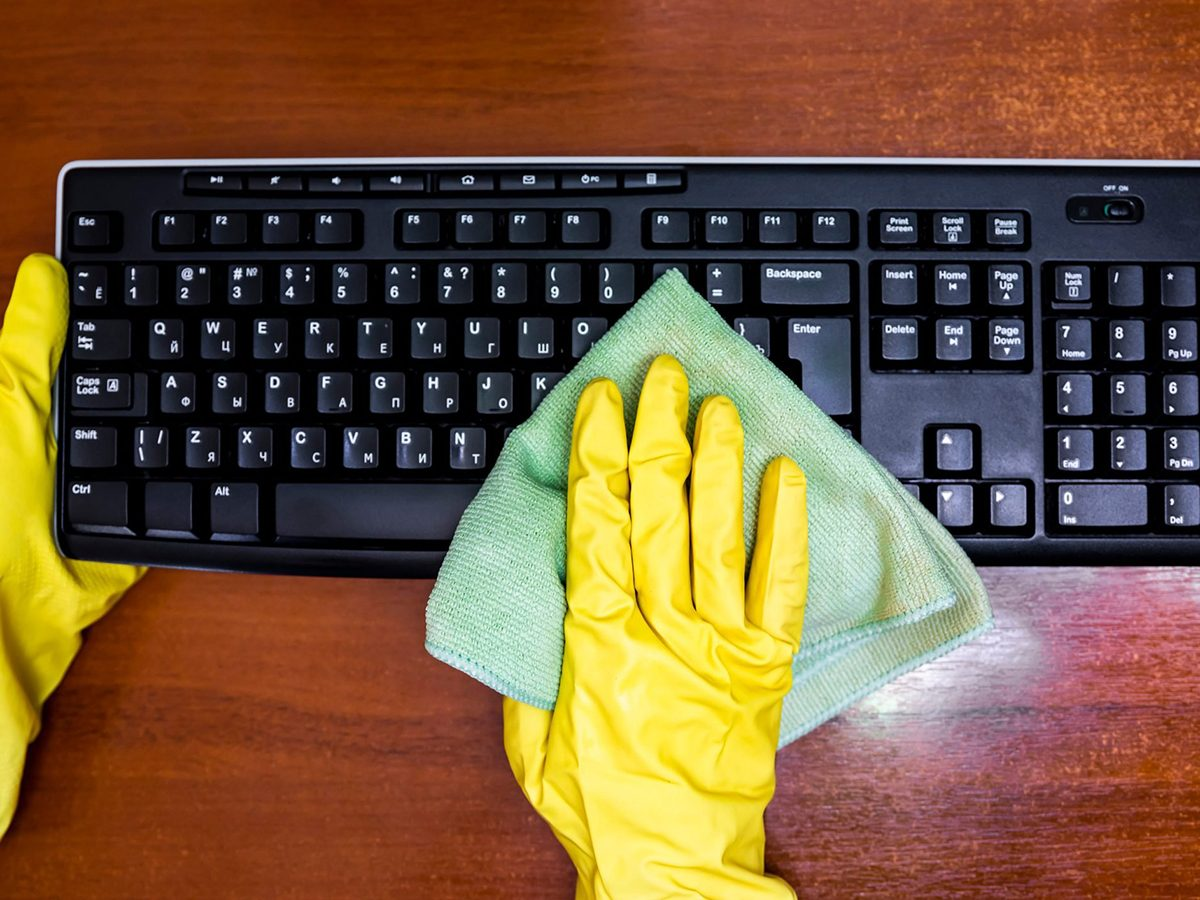 Mistakes you're making with disinfectant - Woman in rubber gloves disinfects the keyboard