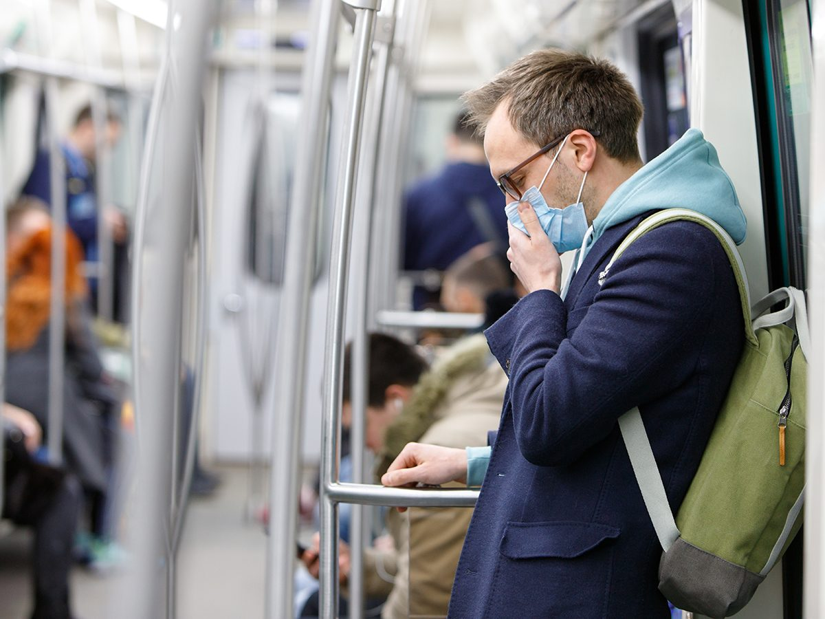 Why some people are more likely to spread COVID-19 - man coughing on subway