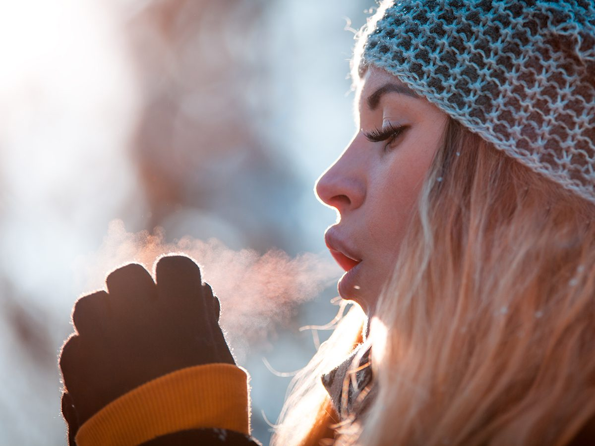 Winter forecast across Canada - cold woman seeing breath