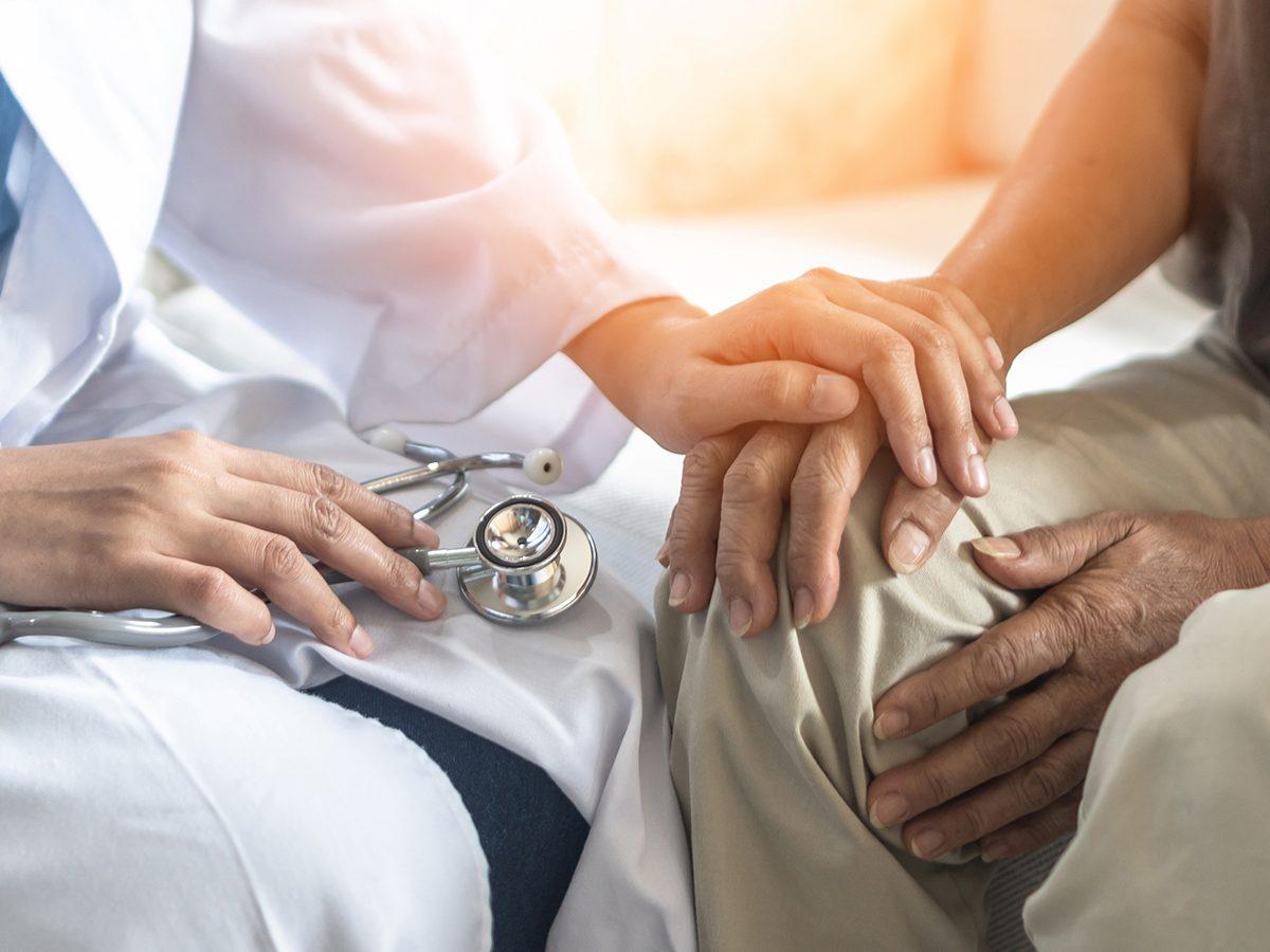Doctor comforting patient with Parkinsons disease