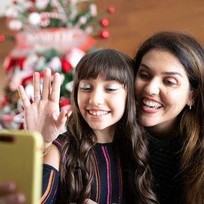 How to celebrate the holidays at home - Mother and daughter making a video conference at christmas time