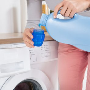 Uses for laundry detergent - Woman pouring detergent in washing machine