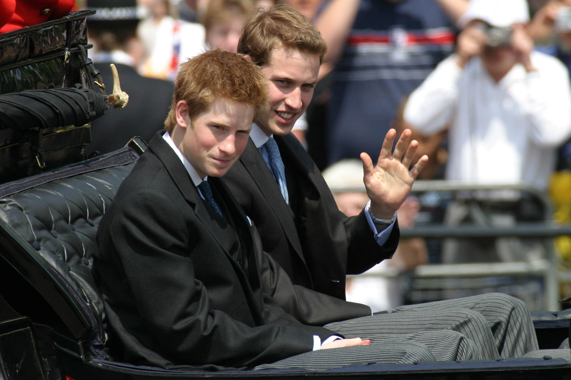 Prince Harry, left, and Prince William in a carriage return to Buckingham Palace from Horse Guards Parade