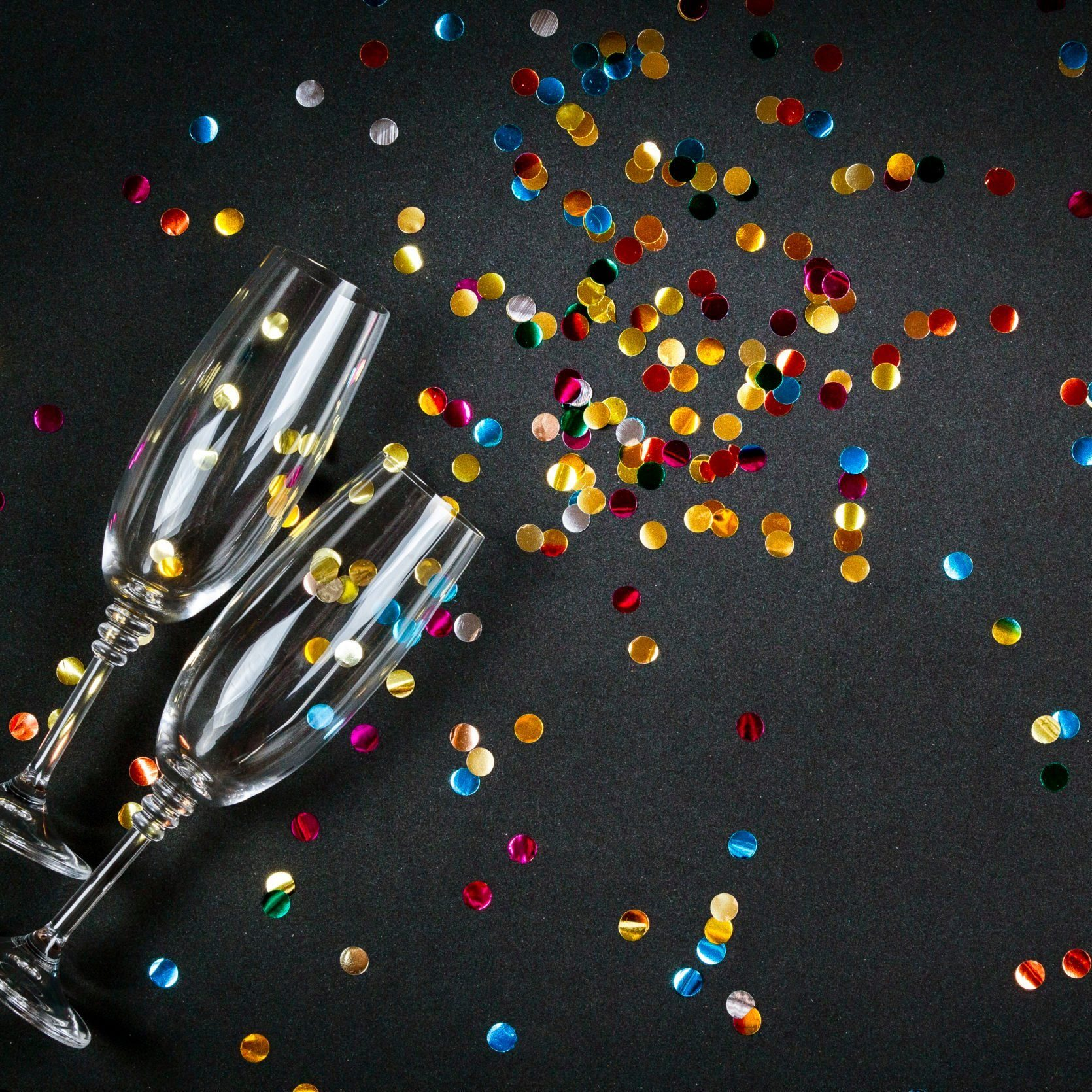 Two glasses of champagne wine with golden decoration of confetti on black background. Celebration composition for festive or party concept. Top view, flat lay, copy space