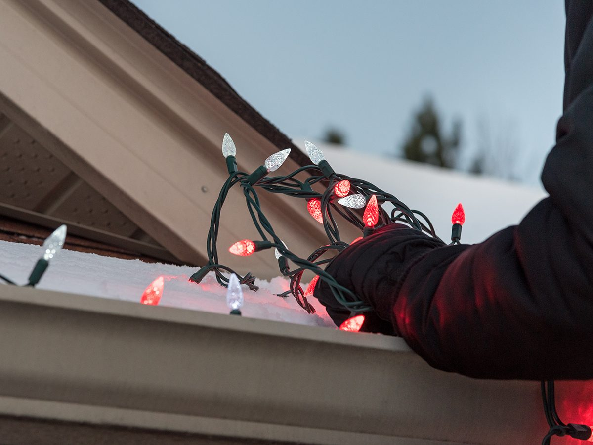 Guide to Christmas lights - Man putting lights on roof