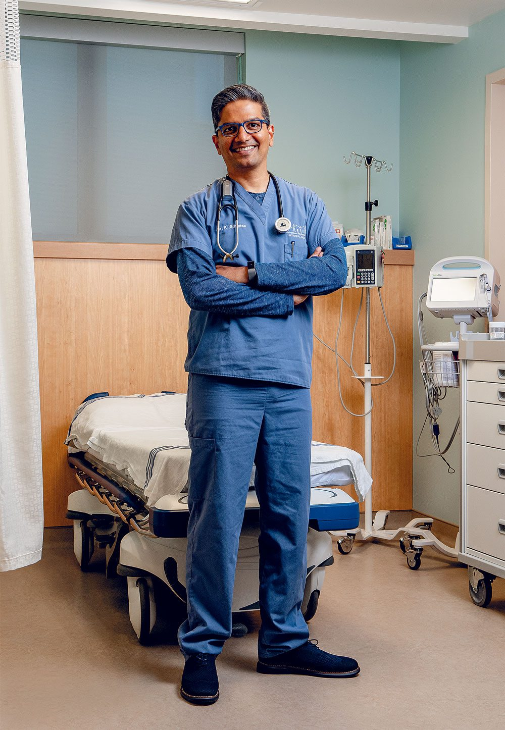 Dr. Kris Srivatsa standing in a hospital room.
