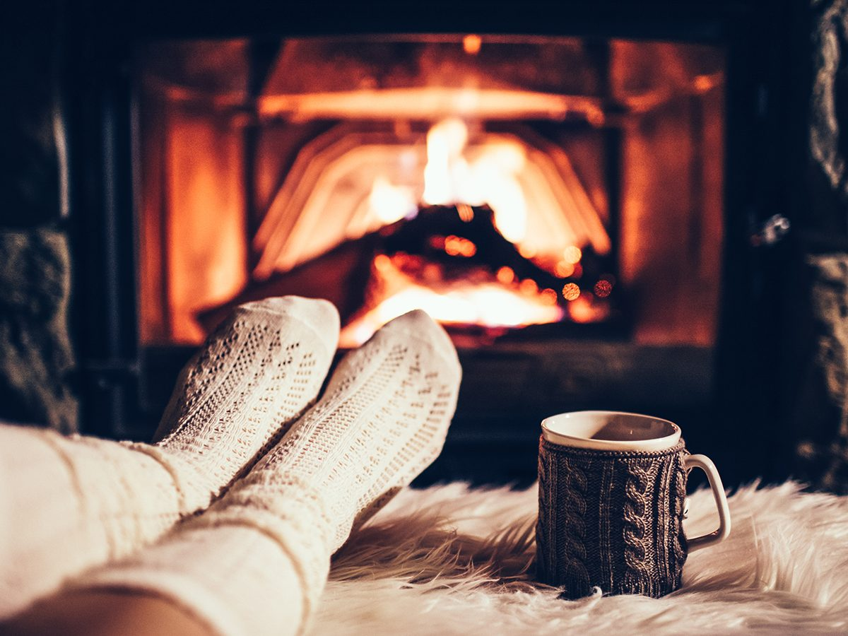 Person sitting in front of fireplace with feet up and mug