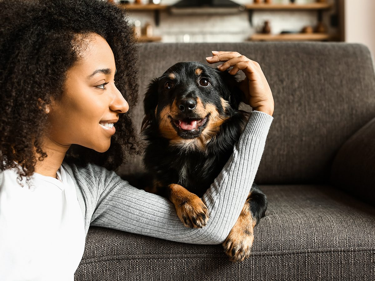 Most popular dog names in Canada - Woman with dog sitting on sofa