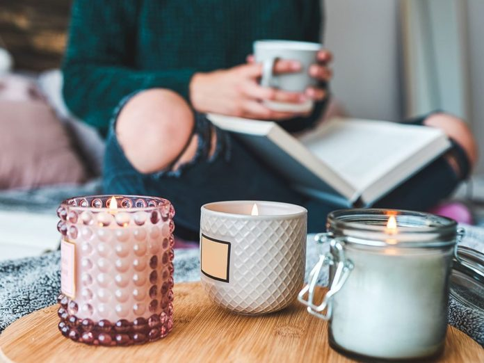 Why you should trim candle wicks - Woman reading a book with three candles lit