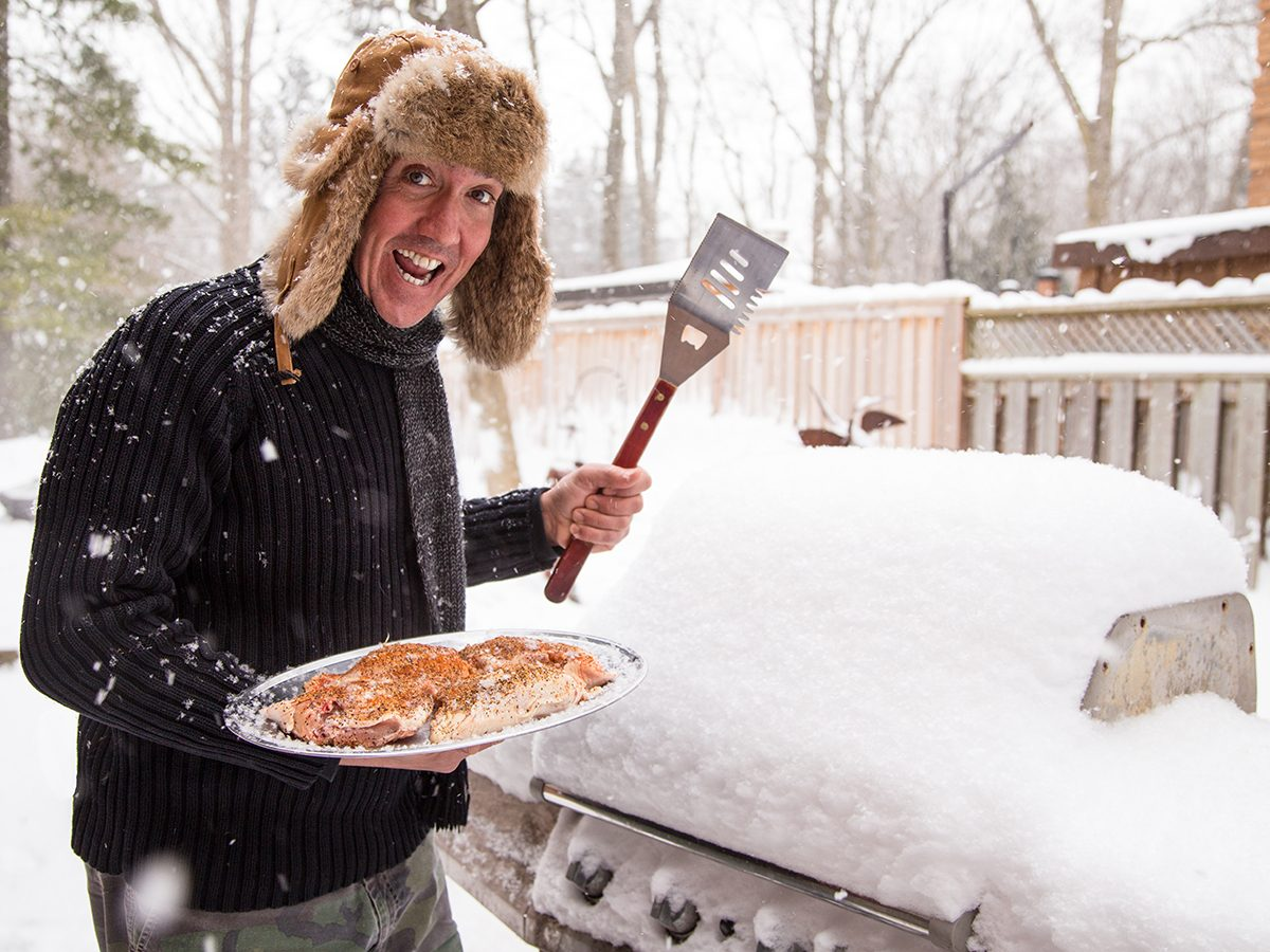 Winter grilling - man wearing winter hat with bbq in snow