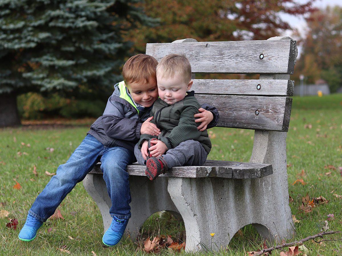 Kids hugging on a bench