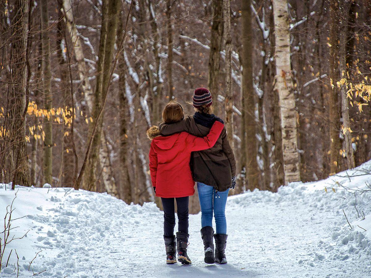 Two girls walking in a snowy woods
