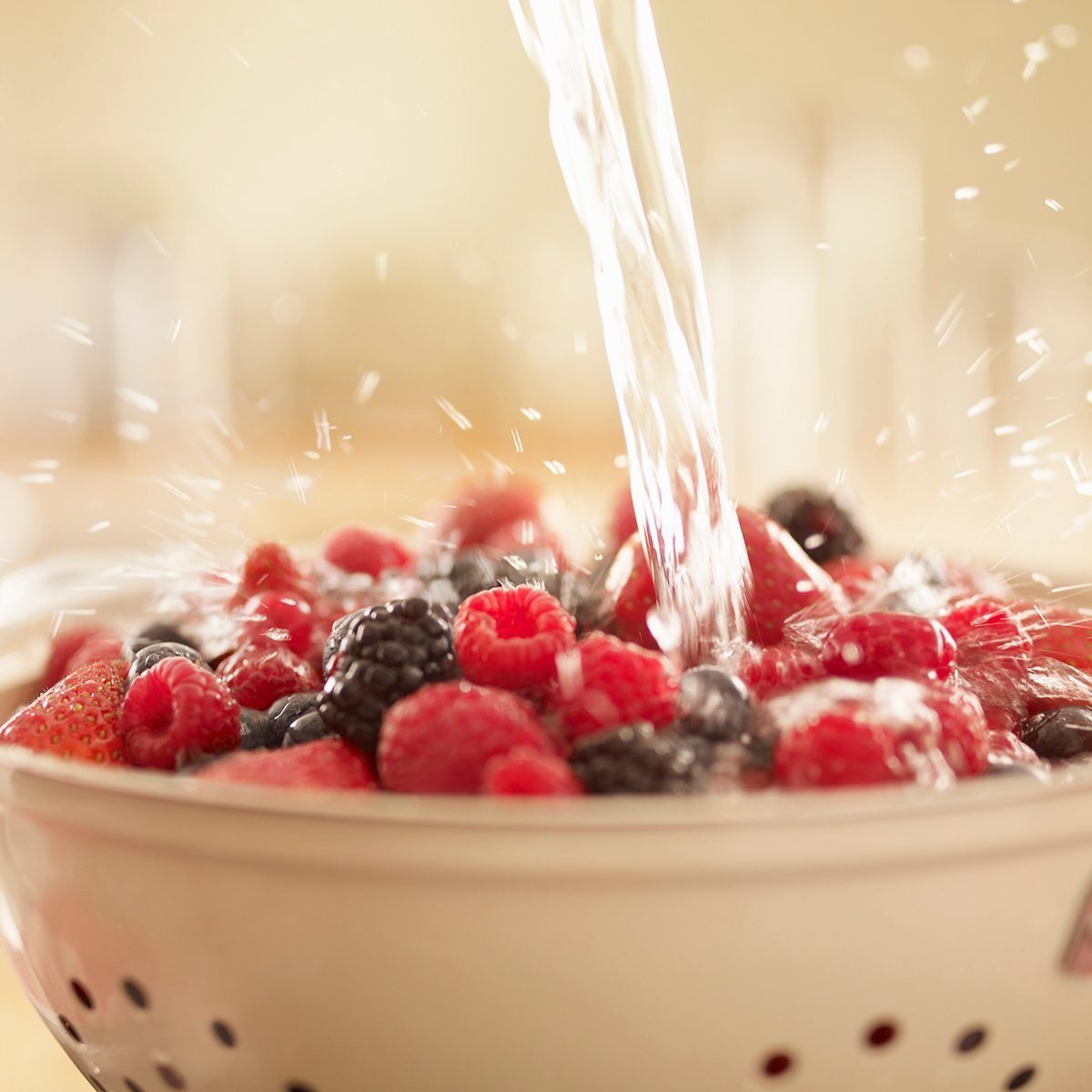 colander uses Water Splashing Over Berries In Colander