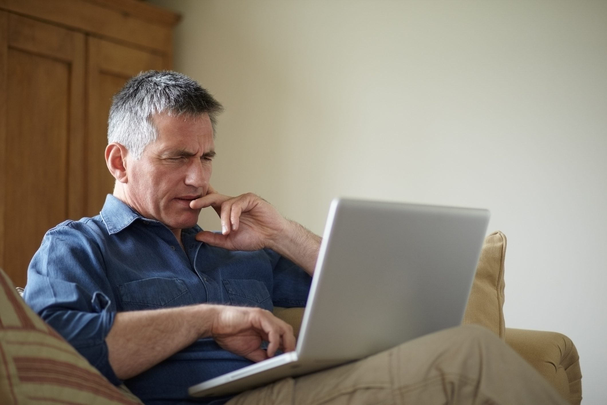 Man using laptop on sofa