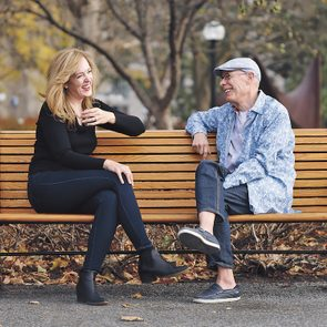 A man and a woman sit outside on a bench talking.