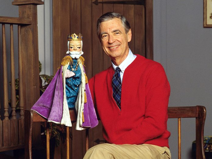 Mr. Rogers sitting and holding a puppet.