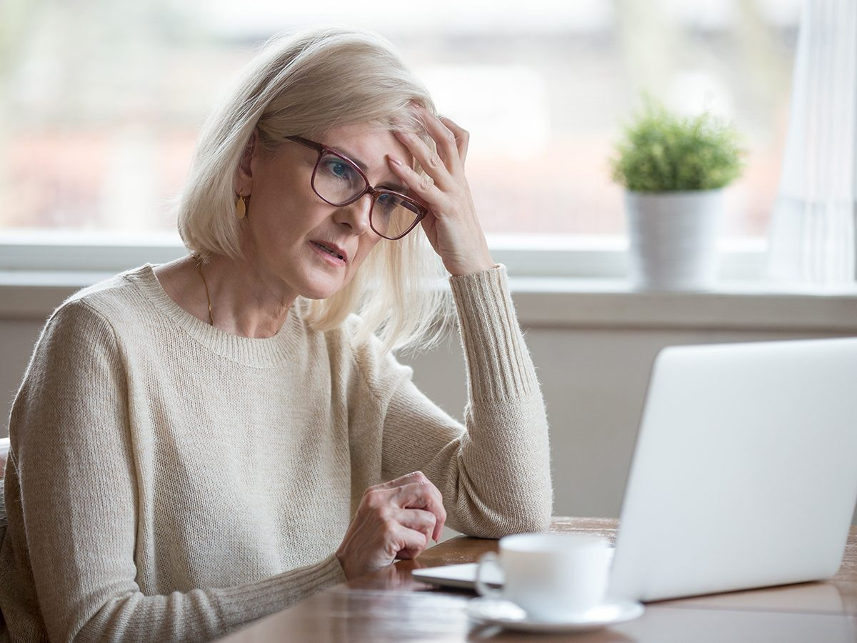 Too much salt - woman feeling brain fog at laptop
