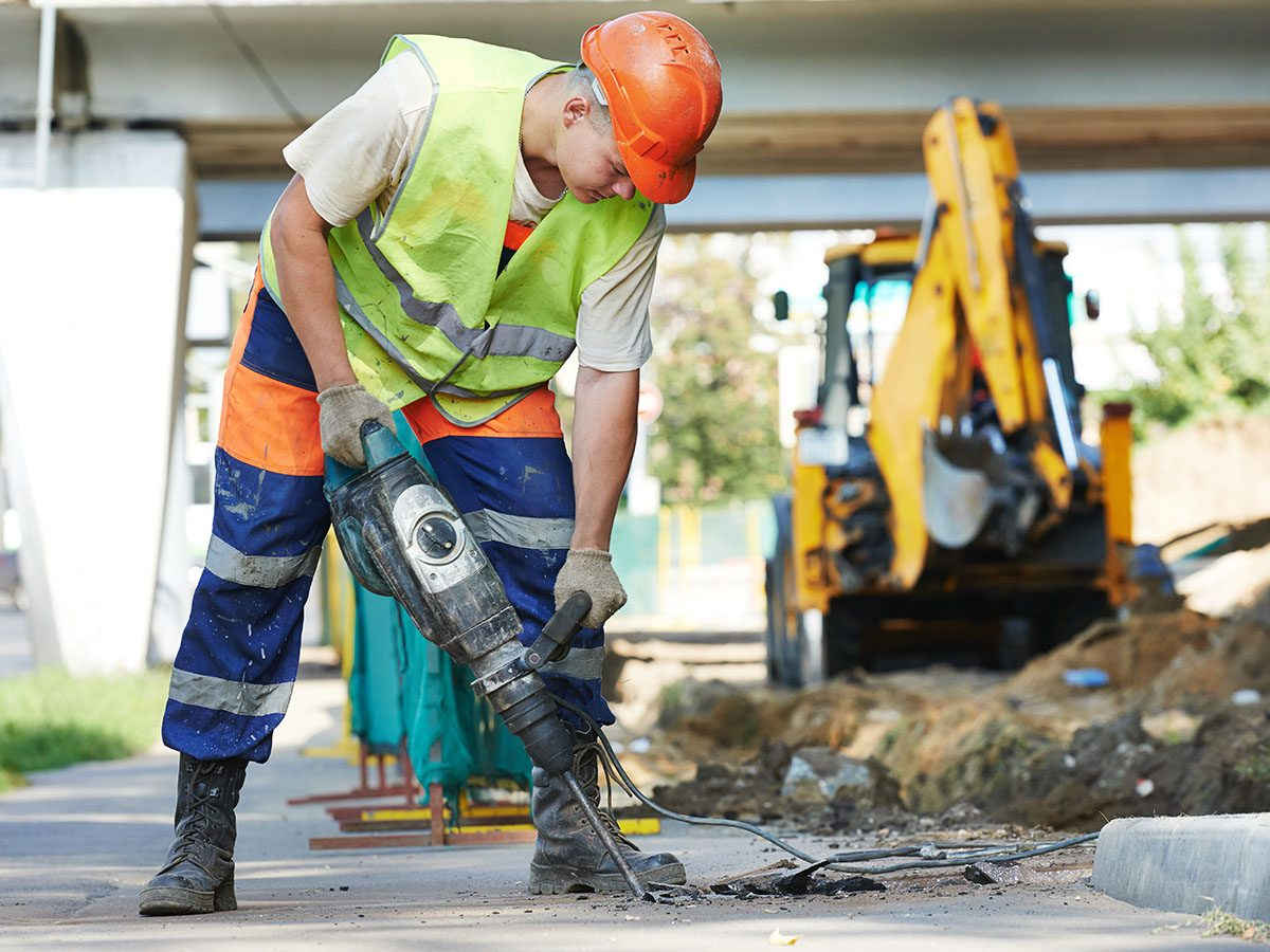 Builder worker with pneumatic hammer drill equipment breaking asphalt at road construction site.