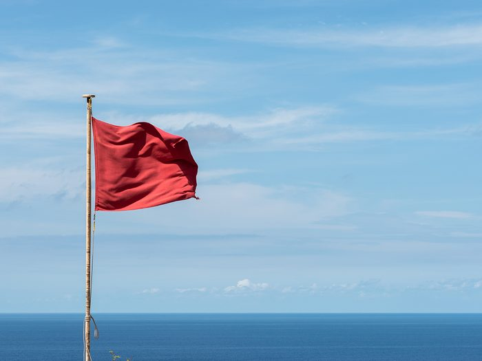 Red flag waving on a pole. Clouds and sea view background. Horizontal View