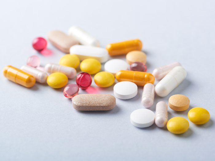 Vitamins and supplements on bright paper background. Concept for a healthy dietary supplementation. Close up. Copy space.