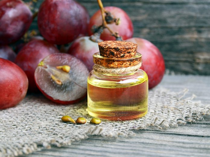 Grape seed oil in a glass jar and fresh grapes for spa and bodycare on old wooden table.Spa,Bio,Eco products concept.