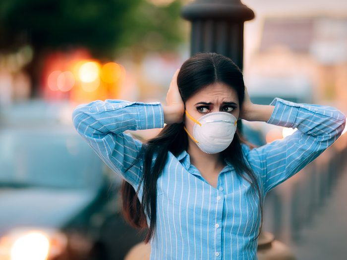 City noise is harmful to your health - woman in mask covering ears