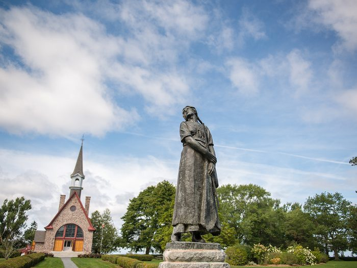 Historical places in every province - Evangeline Statue standing in the Victorian gardens with the Memorial Church in the background, Grand-Pré National Historic Site.