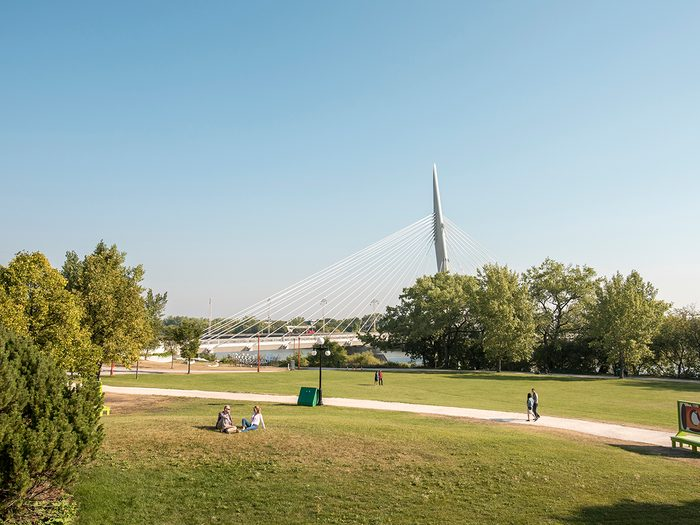Historical places across Canada - Visitors enjoy the green space at Parks Canada Place. The Esplanade Riel pedestrian bridge is in the background. The Forks National Historic Site.
