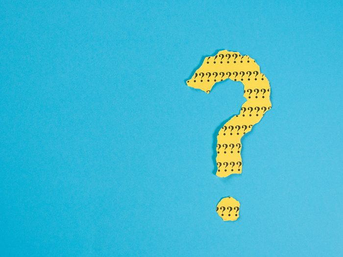 question mark symbol from a teared yellow paper on a blue background with copy space. Concept of FAQ, Q and A, Questions and riddle