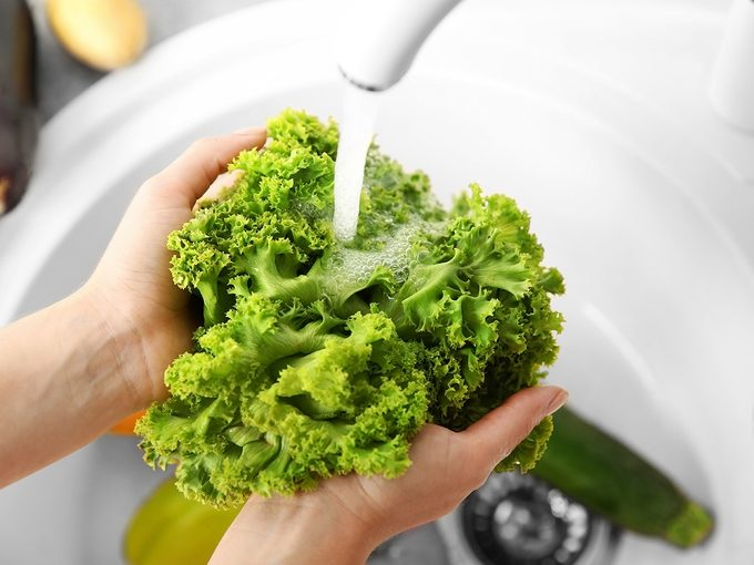 How to wash lettuce - Female hands washing fresh vegetables in kitchen sink